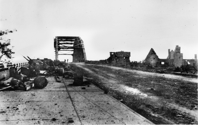 This photograph of the Arnhem bridge was taken after Colonel John Frost's airborne troops had been overwhelmed and the surrounding buildings were razed or cleared by German SS soldiers. The debris from the previous days' fighting still litters the span across the Lower Rhine although the road has been cleared.