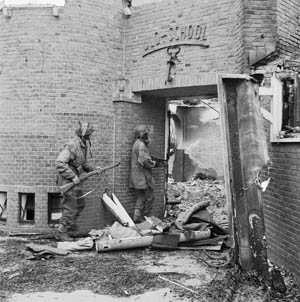 On September 20, 1944, NCOs of the Glider Pilot Regiment search for German snipers through the ruins of the ULO school in Oosterbeek, a town near Arnhem. An empty supply container lies just outside the shattered doorway.