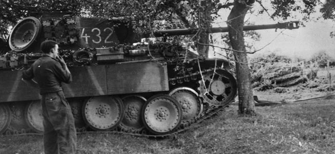 A German PzKpfw. V Panther medium tank lies in ambush amid the cover of trees along a dirt road in France. The Panther mounted a high-velocity 75mm cannon and was protected by thicker armor plating than the American M4 Sherman tank, although the lighter Sherman was capable of greater speed.