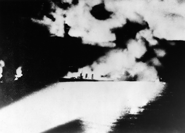 Apparently down by the stern, the cruiser USS Quncy is illuminated by Japanese searchlight beams and pummeled by accurate torpedo and shellfire. The Quincy was one of four Allied cruisers lost at Savo Island, with the Astoria the last to sink.
