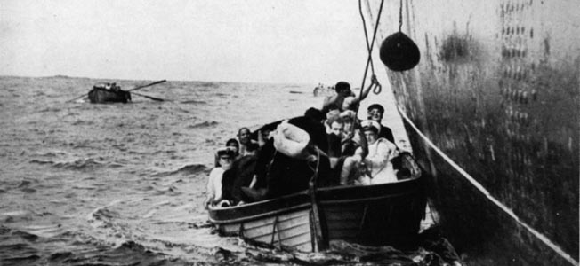 Minutes after the predawn attack by the German raider Atlantis against the Egyptian liner Zam Zam, passengers from the stricken vessel are seen crowding into lifeboats, while the ship itself is listing heavily to port. Atlantis became the most successful of the German surface raiders during World War II.