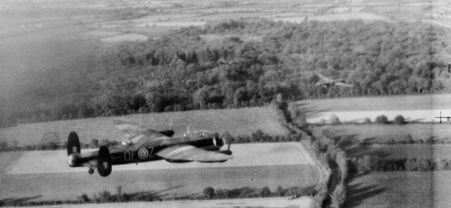 Flying low across the French countryside, an RAF Avro Lancaster heavy bomber participates in a daylight raid on a German engineering facility in October 1942. The RAF later switched to night bombing to help minimize losses to flak and German fighters.