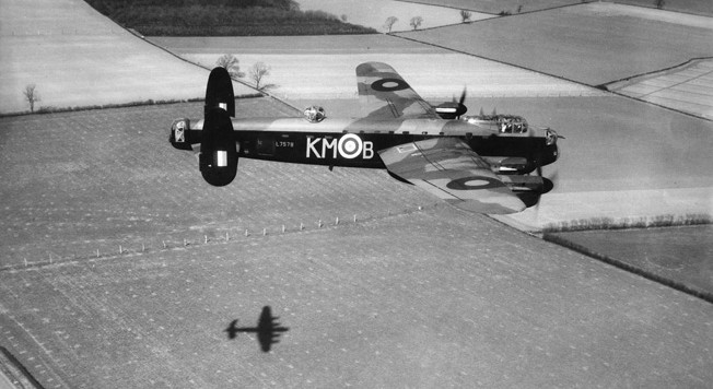 An RAF Lancaster bomber of No. 97 Squadron flies at low level during preparations for the costly raid on the diesel engine assembly facility at Augsburg, Germany. This Lancaster was piloted by Squadron Leader J.D. Nettleton, who led the Augsburg raid and received the Victoria Cross for heroism.