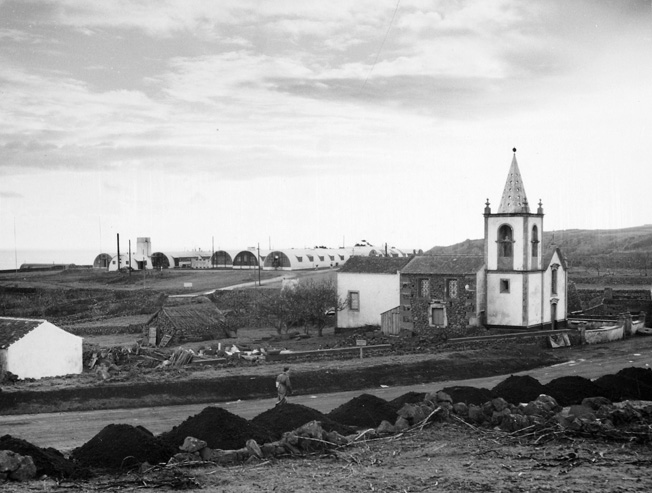 The British hospital at Lagens Field is seen in the background, while a church built by the inhabitants of the island of Terciera lies in the foreground of this photo taken in December 1944.