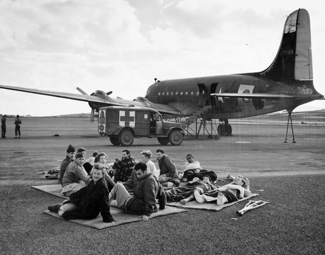 Wounded men lie near the runway at Lagens Field and await transport from the Azores to hospitals in the United States. The transport aircraft shown in the background is the Curtiss-Wright C-46 Commando.
