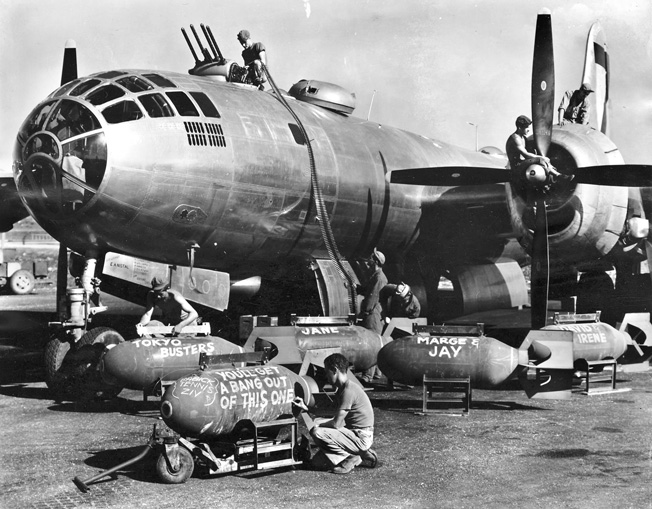 Arming a B-29 of the 500th Bomb Group at Isley Field on the island of Saipan, ground crewmen scrawl messages across some of the ordnance before it is loaded through the gaping bomb bay of one of the aircraft.