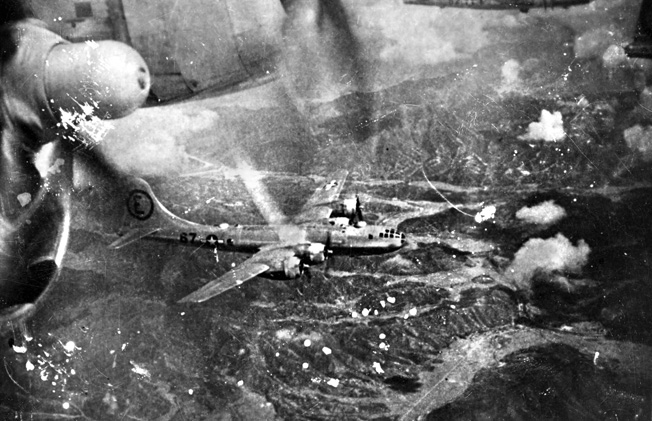 Flying over the rugged, mountainous terrain of Japan, B-29 Superfortress bombers wing their way toward targets in the home islands.