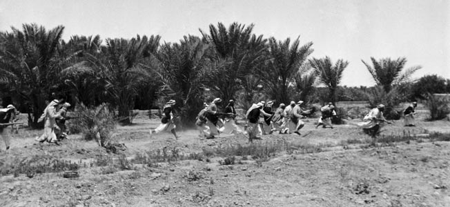 WORLD WAR II: IRAQ, 1941. Tribal warriors in Iraq attacking a British military vehicle at the time of the anti-British revolt during World War II, May 1941. Photographed by Helmut Laux.