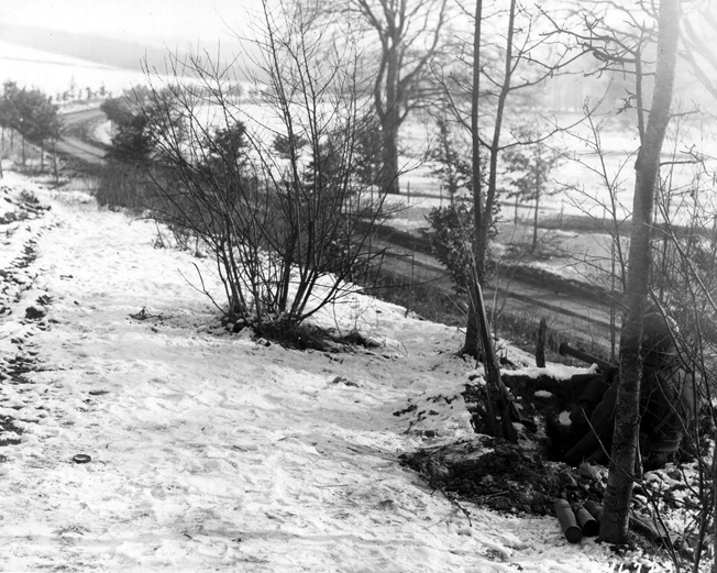 Armed with bazookas, soldiers of the U.S. 101st Airborne Division man a roadblock along the defensive perimeter at Bastogne during the Battle of the Bulge.