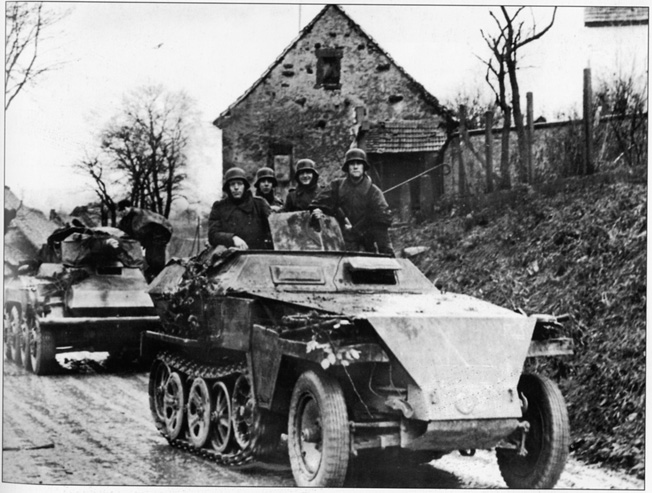 A half-track leads a column of German panzergrenadiers toward the front during the Battle of the Bulge. Veteran troops such as these took on the lightly armed men of Company B, 1/401st Glider Infantry Regiment at Crossroads X and failed to dislodge the plucky Americans in a timely manner.