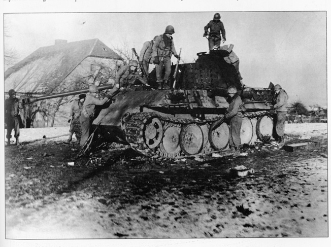 In the aftermath of a fight during which they knocked it out, American soldiers inspect the hulk of a German PzKpfw. V Panther tank. Troops of B Company stood their ground against several German tanks at Crossroads X during the height of the Battle of the Bulge.