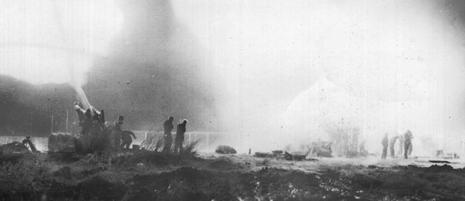 """American artillerymen fire their heavy 155mm """"Long Tom"""" cannons at Japanese positions in support the 38th Infantry Division on the Bataan Peninsula."""