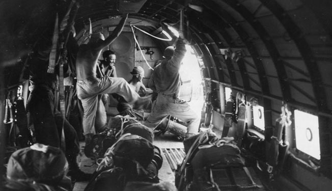 An American airman kicks a packet of supplies out the cargo door of a transport aircraft during the 38th Division offensive on the Bataan Peninsula. The difficult terrain required resupply by air, particularly during the struggle for control of Zig Zag Pass.