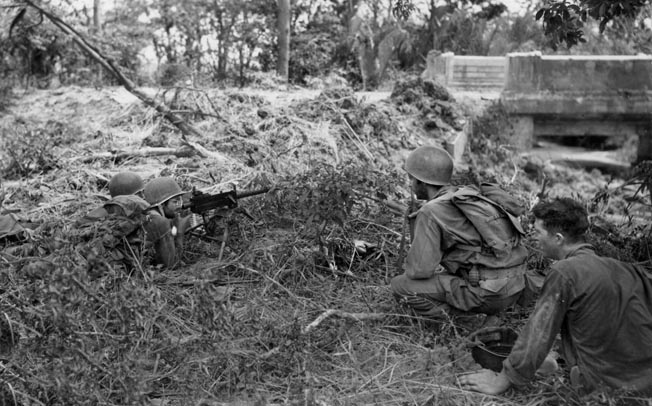 A pair of American soldiers occupy a foxhole with a .30-caliber machine gun at the ready while other members of their squad approach. The sluggish advance against the Japanese on the Bataan Peninsula took its toll on the U.S. troops, while the enemy often fought to the death.
