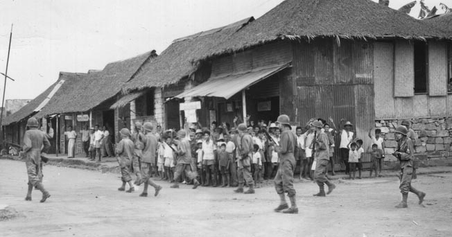 The townspeople of Balanga on the Bataan Peninsula turn out to greet soldiers of the 149th Infantry Regiment, 38th Division, steadily advancing against the Japanese. The circumstances of this trek, following the route of the infamous Death March of 1942, were quite different from the earlier tragic event that claimed many American and Filipino lives.
