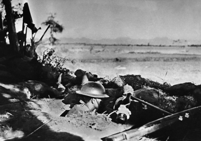 Wearing the World War I-style doughboy helmet, an American soldier crouches in his foxhole on Bataan in April 1942.  Making use of every available weapon, this soldier has an improvised Molotov cocktail at the ready to hurl against the advancing Japanese.
