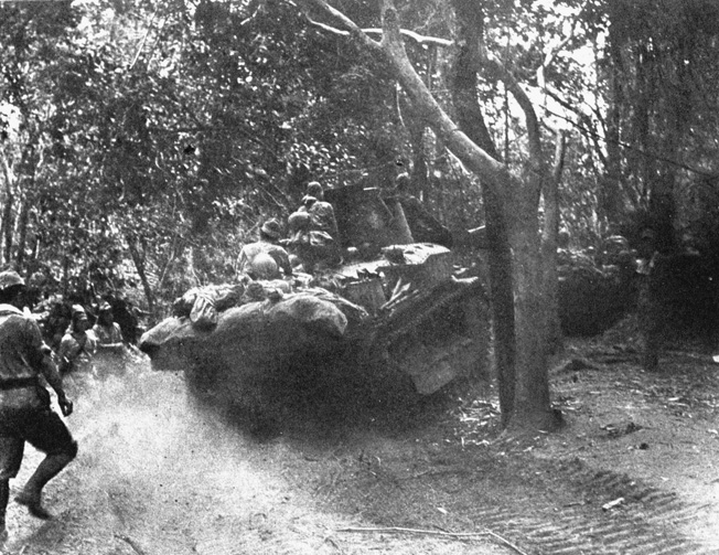 Japanese infantry and light tanks advance along a jungle trail on the Bataan Peninsula.