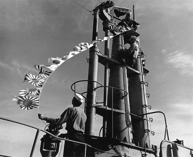 As she heads home from a combat patrol on May 22, 1945, the submarine USS Batfish flies battle flags from her mast.