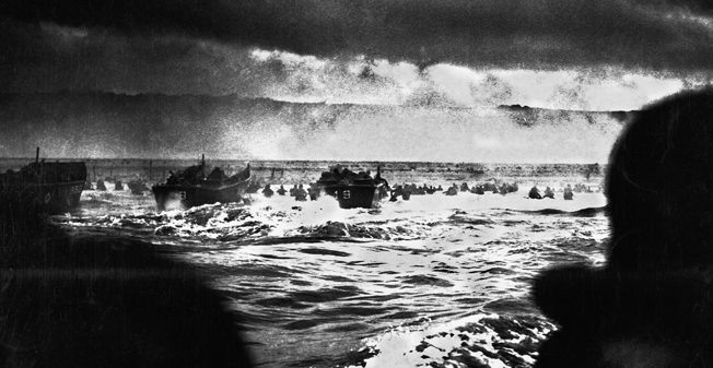 Landing craft churn toward Omaha Beach during the opening minutes of D-Day, June 6, 1944, while some soldiers are seen wading through the chest-high surf.