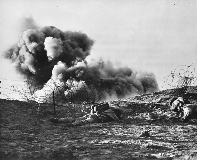 During training exercises in Britain, American soldiers blast barbedwire entanglements with a Bangalore torpedo, an explosive that was supplied to the troops in tubular sections and assembled on the beach. One soldier is conspicuous with the fuel tanks of his flamethrower visible.