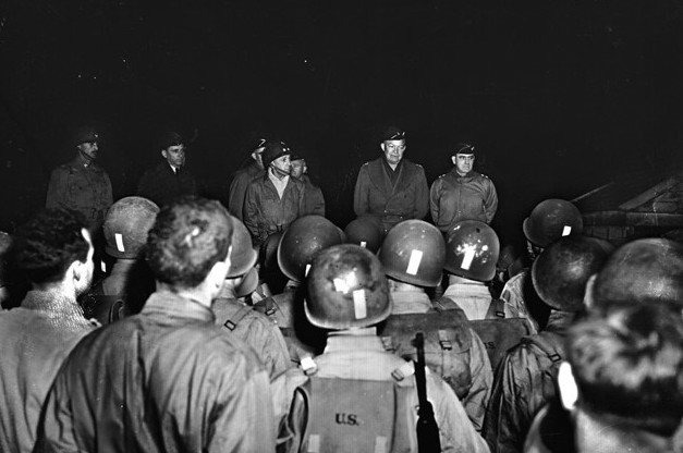 General Dwight D. Eisenhower (center) addresses soldiers of the 116th Regiment, 29th Division during training exercises on February 4, 1944. Eisenhower is flanked by Major General Charles Gerhardt (left), commander of the 29th Division, and Major General Leonard Gerow (right), commander of the U.S. Army's V Corps.