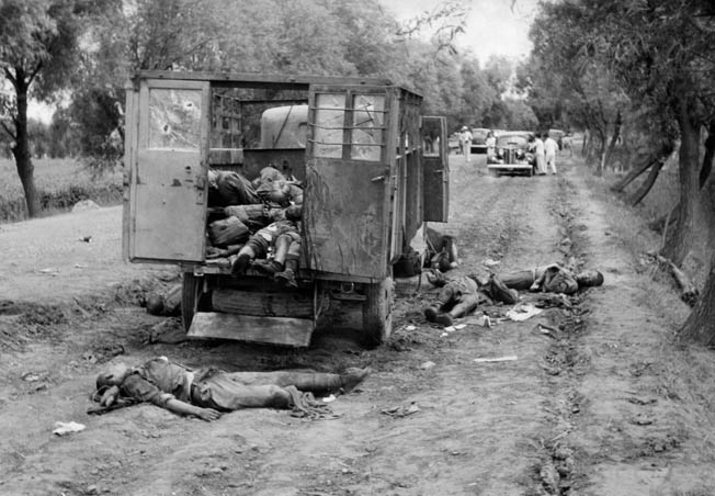 Attached during the retreat from Beijing, dead of the Chinese 29th Army and their destroyed vehicles litter a road outside the city. Onlookers have stopped their cars in the distance.
