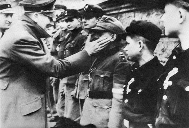 During one of his last public appearances before committing suicide in the Führerbunker, Adolf Hitler pats a young member of the Hitler Youth on the cheek after awarding him the Iron Cross.