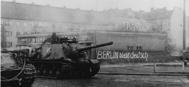 """A Soviet armored vehicle speeds past a building with the slogan """"Berlin will remain German"""" scrawled on one of its exterior walls."""