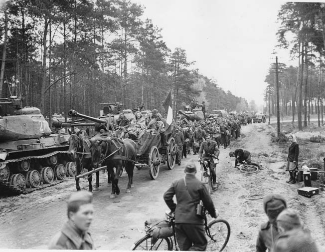 Fleeing the fighting during the Battle of Berlin, German refugees and Allied soldiers freed from prisoner of war camps plod westward toward an uncertain future. Soviet tanks line the side of the road.