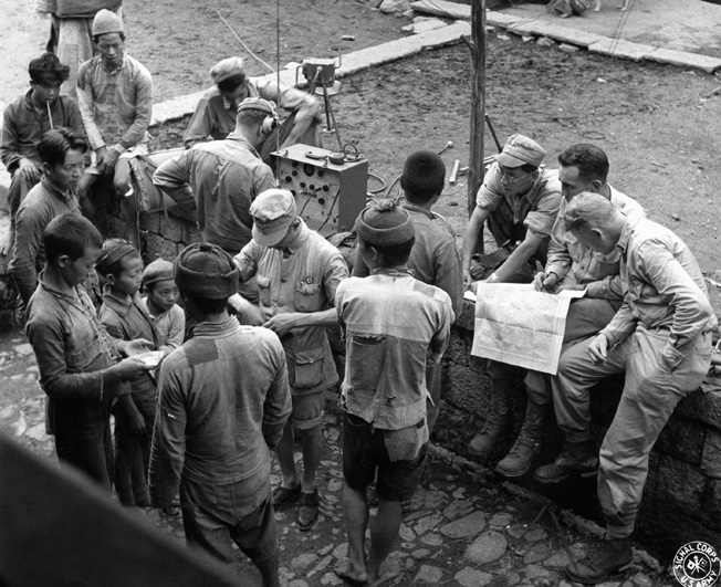 Questioning a local villager as to their position, members of Y Force stop in a remote Chinese village for the night. Utilizing a map, they attempt to orient themselves during their foray into northern Burma and work to establish radio communications.