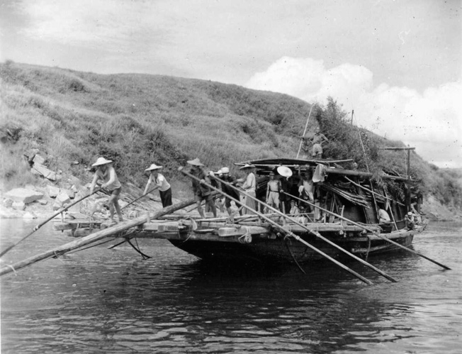 Laden with Chinese commandos, sampans make their way down the Liu River en route to attack Japanese positions in the hills near Tanchuk.