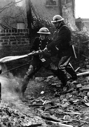 Richard Southern and R.H. Betts, auxiliary firemen in London, train their hoses on a flaming house while another burns just behind them. A number of firefighters died during the Blitz.
