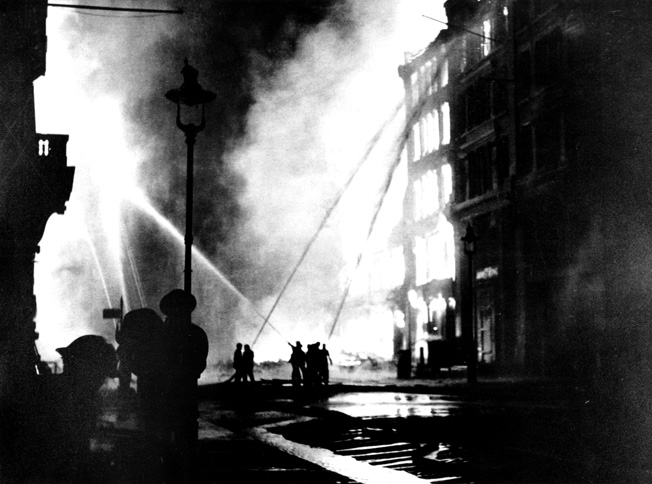 By the end of 1940, nearly 20,000 incendiary bombs had been dropped on London by the Luftwaffe. The London Fire Brigade, several of its members shown here silhouetted against a burning building and directing streams of water toward the flames, performed heroically while battling stricken areas.
