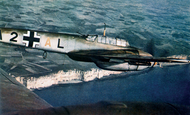 Flying above the famed white cliffs of Dover and the English Channel, a twin-engine Messerschmitt Me-110 of the Luftwaffe provides escort duty to German bombers.
