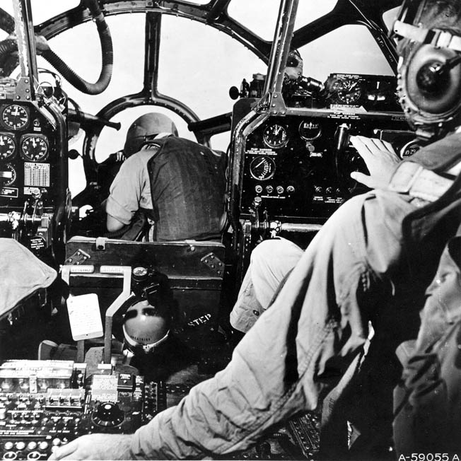 "A B-29 Superfortress bombardier, forward of the pilot and co-pilot, is shown at work in his ""office."""