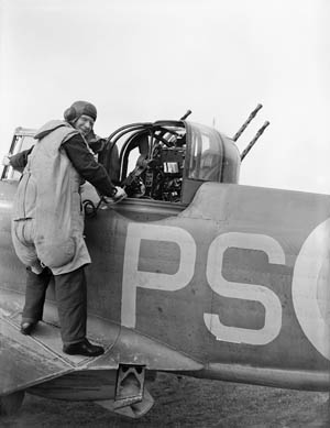 Preparing to enter the gun turret of his Boulton Paul Defiant Mark I fighter at its base at Kirton-in-Lindsey, Lincolnshire, a gunner of No. 264 Squadron, RAF, smiles confidently over his shoulder. The Defiant was obsolete by the time this photo was taken in August 1940.