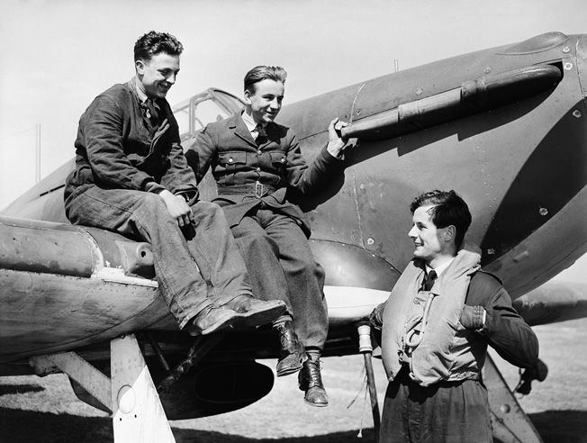 Squadron Leader Peter Townsend chats with two ground crewmen as they sit jauntily atop the wing of his Hawker Hurricane fighter based at Wick, Scotland. The Hurricane proved more effective against German bombers, while Spitfires attacked the enemy fighters during the Battle of Britain.