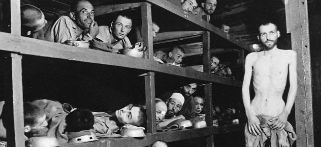 This interior view of a barracks at Buchenwald reveals the stifling confines of the sleeping area. Some of the prisoners us their food bowls as pillows. Disease spread rapidly in such close quarters and accounted for many deaths.