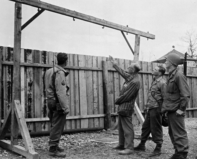 Following the liberation of Buchenwald, an inmate shows two American soldiers the prison gallows.