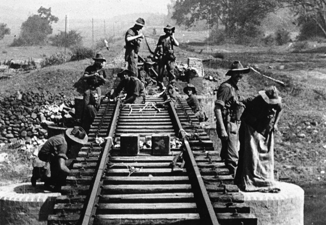 Wearing large-brimmed hats to ward off the tropical sun, engineers of the 77 Brigade wire a section of railroad track with explosives.