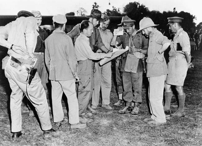 Brigadier Orde Wingate, wearing a pith helmet, confers with Allied staff officers prior to taking off for the Chindit base at Sylhet, Assam, India.