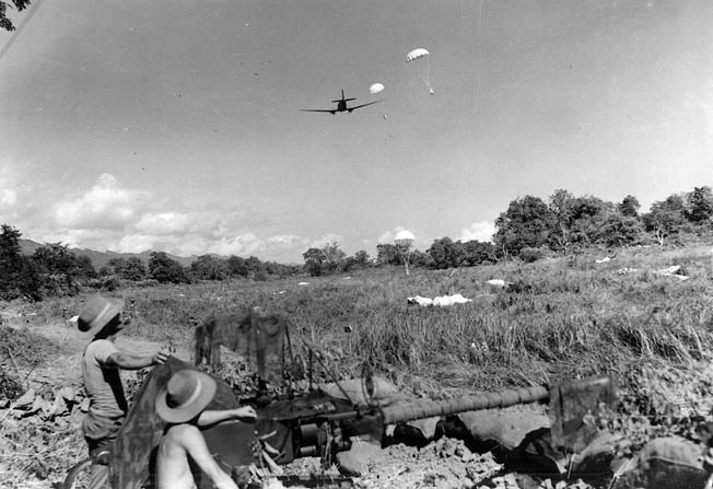 British soldiers, one of them shirtless, man a field gun and keep watch for enemy troop movements as a Douglas C-47 transport aircraft drops supplies by parachute.