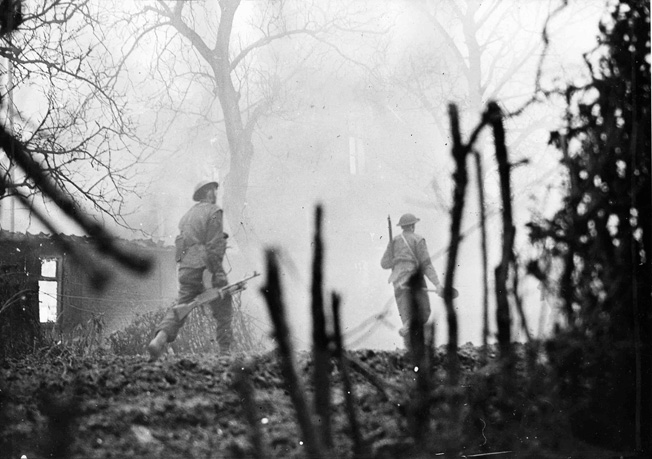 During their drive to the west bank of the Rhine, Canadian soldiers hurry through Calear. Resistance at this point consisted mainly of thickly sewn minefields and snipers, which sometimes held up large formations of troops.