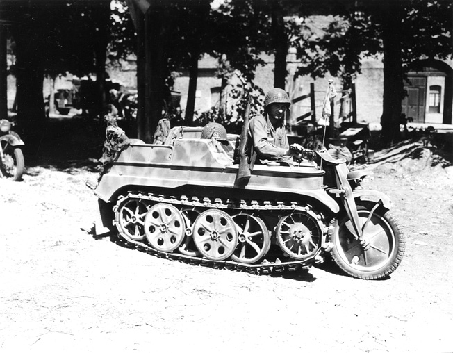A paratrooper with the 101st Airborne Division tries out a German half-track motorcycle, known as a kettenkrad, in Carentan, France.
