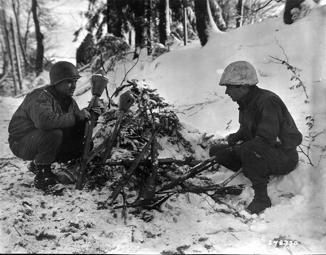 Soldiers from the First Infantry Division examine rifles and Panzerfausts left behind when the Germans were forced out of Schoppen, Belgium in January 1945.