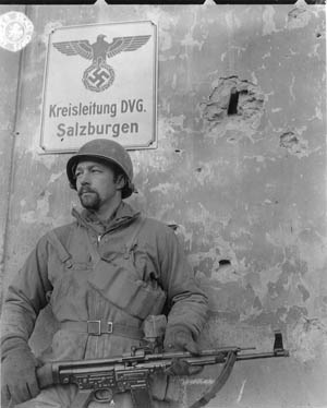 Sergeant Oakly M. Rath holds a captured German Sturmgewehr 44 in front of a chateau in Salins, France.
