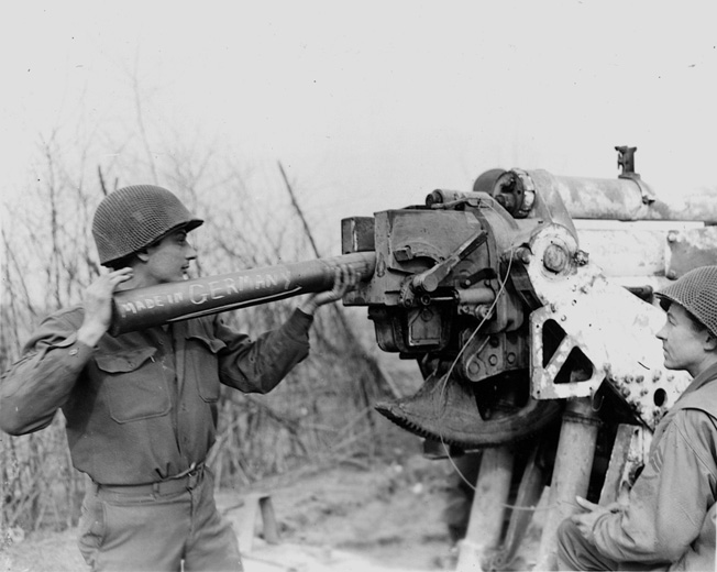 "Turning the enemy's own 88mm gun on them, a soldier loads the notorious weapon with a shell inscribed ""Made in Germany"" and prepares to fire across the Rhine River."