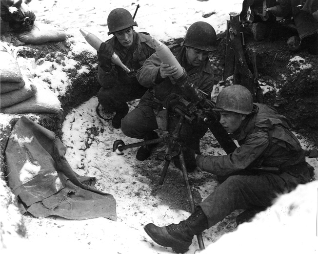 Americans fire a captured German mortar toward enemy positions.