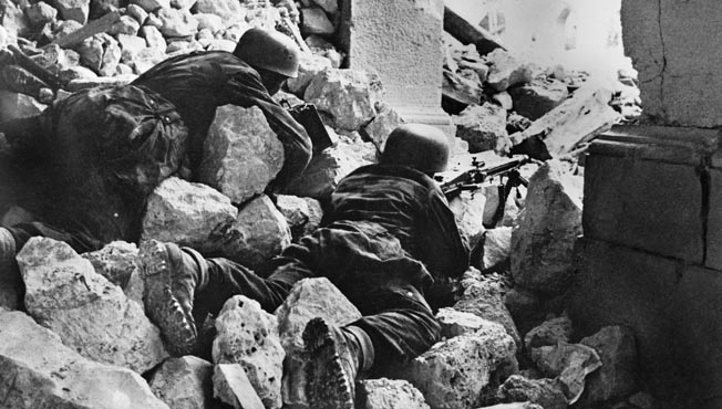 A pair of German paratroopers use the rubble of the destroyed abbey as an ideal position for their MG42.