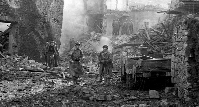 American and French colonial troops pick their way through a village destroyed by the German Luftwaffe near Cassino, January 14, 1944.